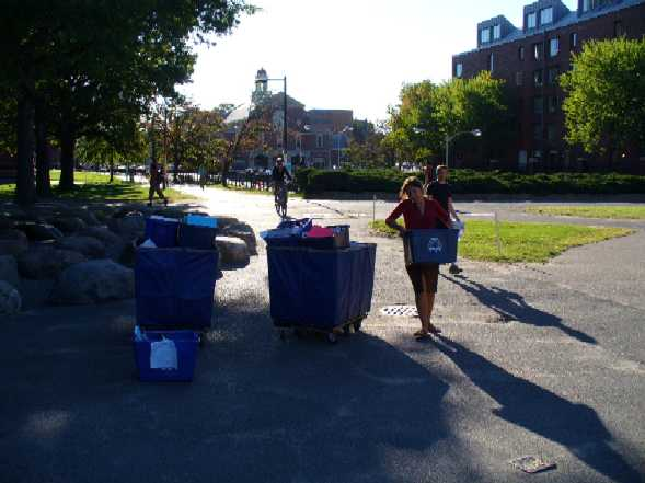 Carrying tubs of used course packs for the book sale.