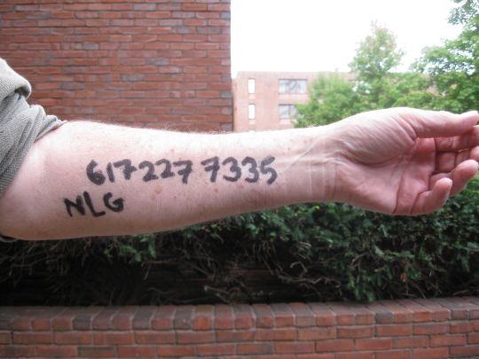 My arm with the number of the Boston office ot the National Lawyer's Guild on it.