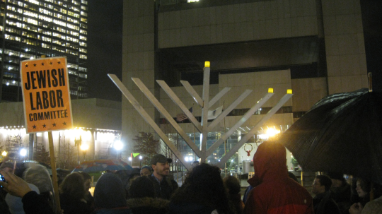 The Jewish Labor Committee and friends Occupy Hanukkah and the Holidays at Dewey Square Boston. The Federal Reserve Bank of Boston is in the background.