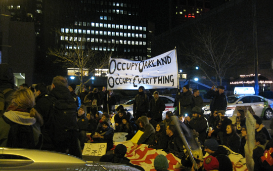 Occupy Boston marchers sitting down in the street in front of the Prudential Center