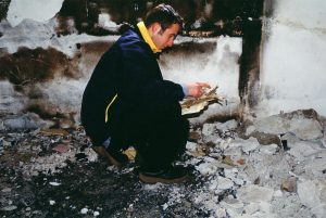A young man squatting on the ground to pick up and look at torn and burned religious texts inside the village mosque, torched by Serbian soldiers in 1999. The man is photographed from the side, wearing a dark clothing. The ground is rabbled with pieces of concretes and debris. In the background, burned marks on the concrete wall is visible.