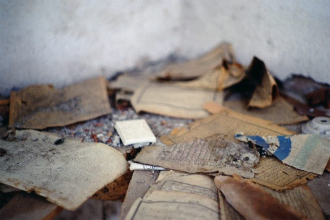 Close-up image of torn and desecrated pages from Qur'ans and religious books, inside the burned-out village mosque.