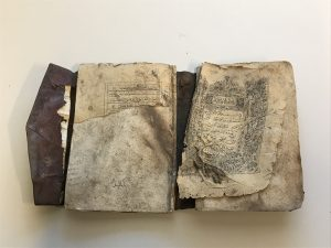 Burned book of a Qur'an, opened to show its pages ripped from its binding and partially burned. The edges of book pages are burned.