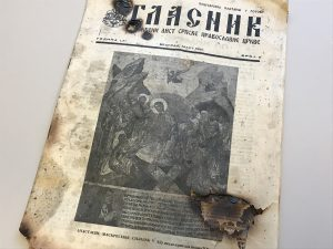 A monthly church bulletin, written in Serbian, with partially burned marks. The cover of the bulletin includes a black and white image of religious painting. A couple of burned holes were made from the fire.