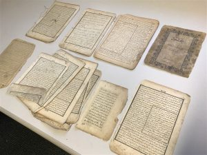 A selection of the damaged pages of books and manuscripts laid on a table. There are two rows and four columns of stacked pages.