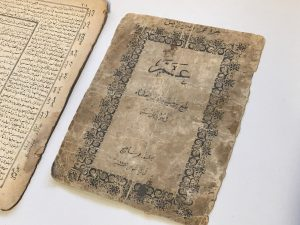 Close-up image of the cover of a damaged and desecrated book. The cover includes an ornate border, but the text is difficult to read due to the fire damage.