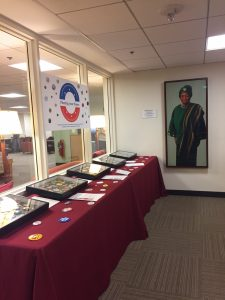 "Display of political buttons in the HKS library. Five display boxes contain political buttons on different themes. A bright poster in the shape of a political button hangs over the exhibit. The title reads, ""Pinning your Hopes."""