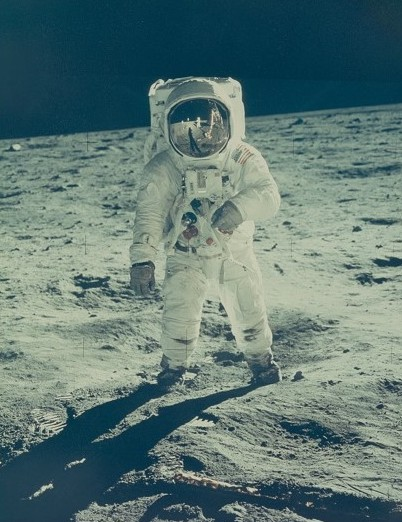 Astronaut Buzz Aldrin stands on the moon, with the image of astronaut Neil Armstrong reflected in Aldrin's helmet.