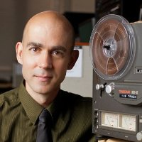 headshot of Lybarger w/ reel-to-reel tape player