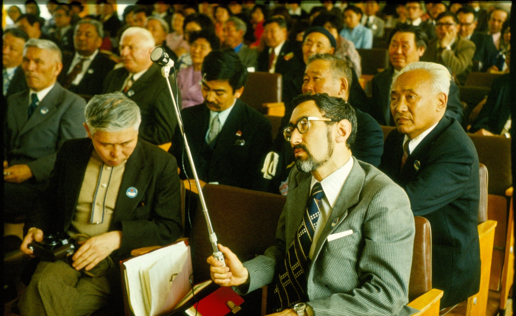 Dressed in a grey suit and holding a microphone on an extension stick, Eduard Alekseyev sits in a crowded auditorium. The date and location of this photograph are unknown.