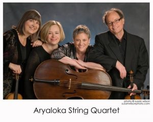 Four musicians are smiling and holding their instruments: two violins, a viola and a cello.