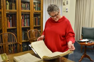 Sandi-Jo Malmon stands in front of a table holding an oblong manuscript score. She is wearing glasses and a red sweater.