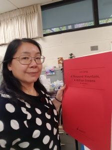 Lingwei Qiu is wearing a black and white top. She is holding a red score by Lei Liang entitled A Thousand Mountains, A Million Streams.