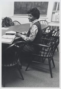 Eileen Southern, smiling, sitting in three quarter profile in a seminar-style classroom, with an open binder of papers and a copy of The Music of Black Americans on the table in front of her.