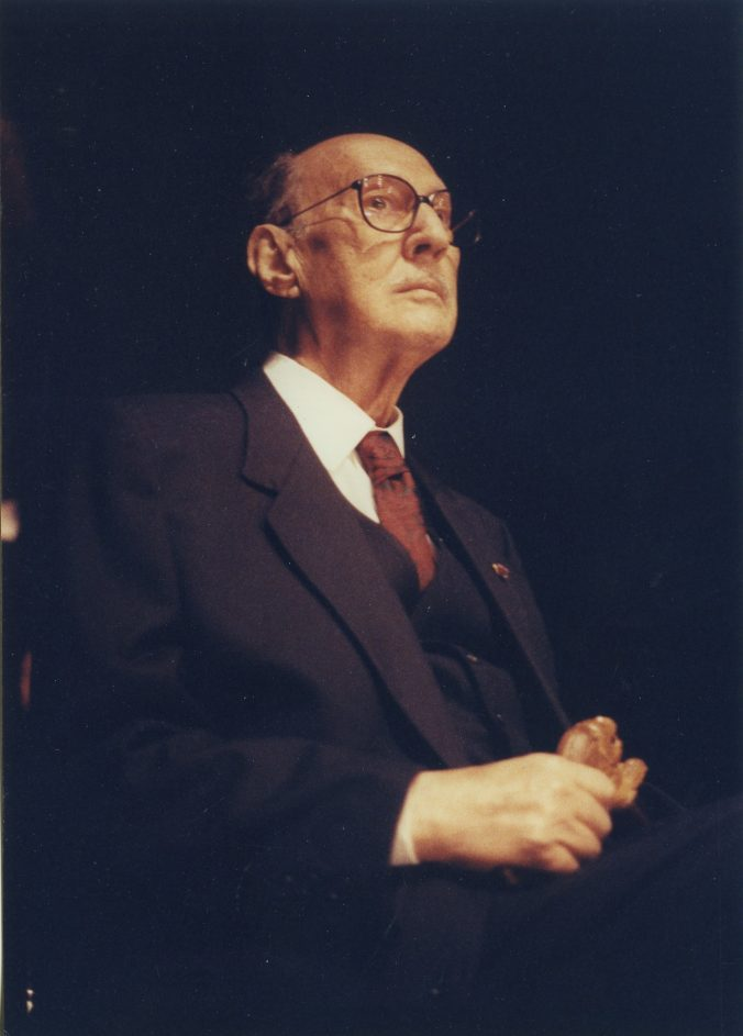 In this half-body photographic portrait, the composer Aziz El-Shawan is depicted wearing a three-piece dark suit and looking into the distance.