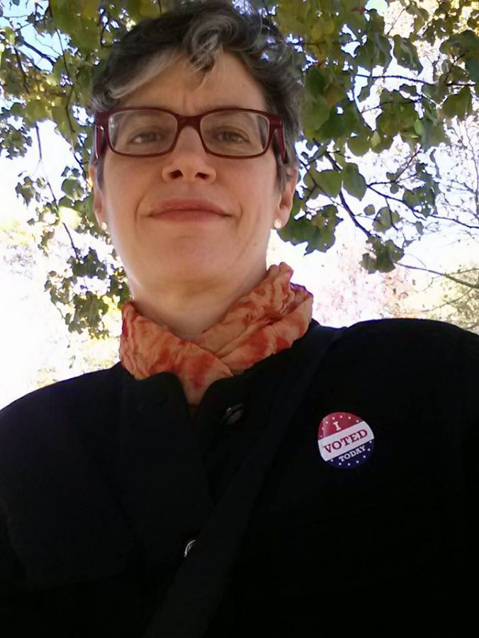 Senior Music Cataloger Anne Adams is posed with a green-leaved tree behind her. She is wearing a black pantsuit with an I Voted Today sticker on the lapel.